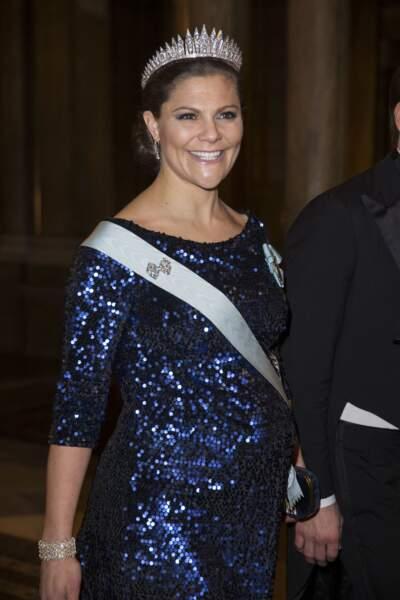 Toujours souriante, la princesse Victoria de Suède, enceinte et ravissante en robe strassée, le 11 décembre 2015.