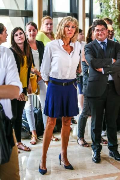 Brigitte Macron à Bercy en chemise, jupe plissée courte et escarpins, le 30 août 2016.