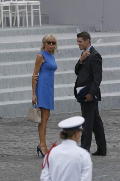 Brigitte Macron en robe courte d'un bleu pervenche lors du défilé du 14 juillet 2015.