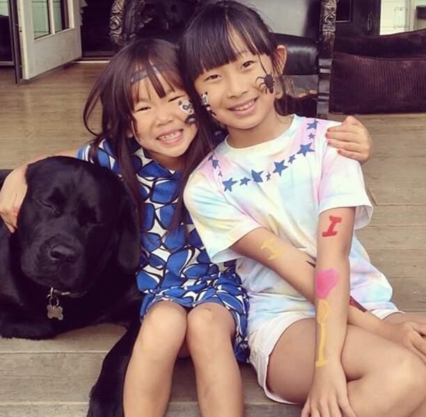 Jade et Joy Hallyday posent avec le chien de la famille.