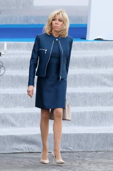 Brigitte Macron et son gimmick mode : le perfecto porté sur une robe droite, ici le 14 juillet 2017.