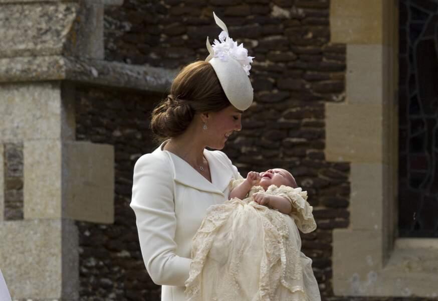 Kate Middleton après le le baptême de la princesse Charlotte qu'elle tient dans les bras, à l'église St. Mary Magdalene à Sandringham, le 5 juillet 2015.