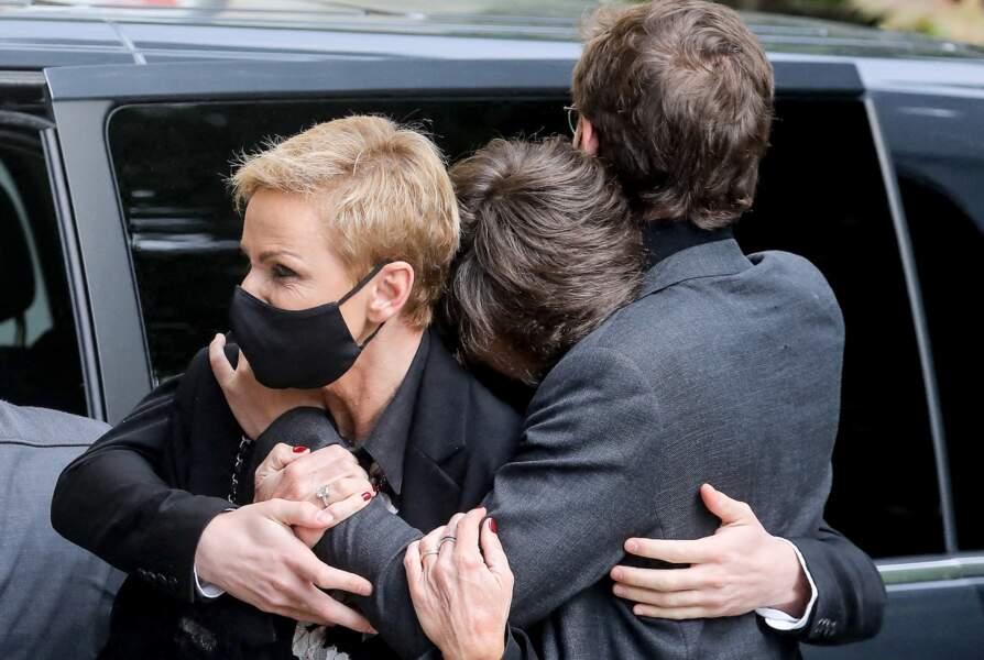 Karin Rénier très émue, épaulée par ses deux fils Oscar et Jules aux obsèques d'Yves Rénier.