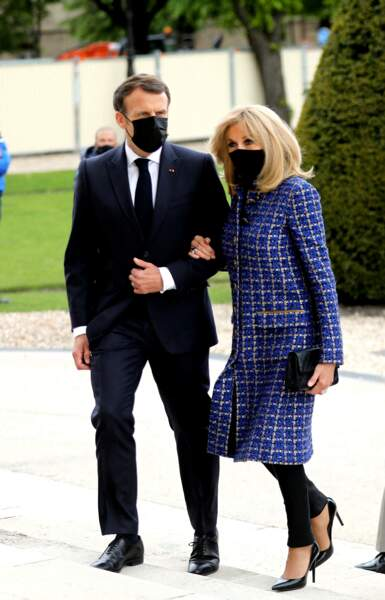 Brigitte Macron ultra chic en manteau long en tweed bleu, pantalon cigarette, talons hauts et pochette siglée pour le bicentenaire de la mort de Napoléon 1er, le 5 mai 2021