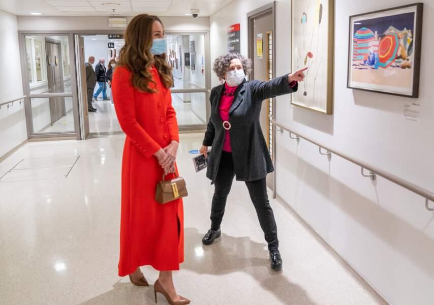 Kate Middleton, duchesse de Cambridge, dans son long manteau rouge et son sac à main en cuir DeMellier, et une paire d'escarpins Ralph Lauren.
