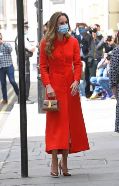 Kate Middleton, duchesse de Cambridge, dans son long manteau rouge et un sac à main en cuir DeMellier, le 7 mai 2021, pour la sortie de son livre.