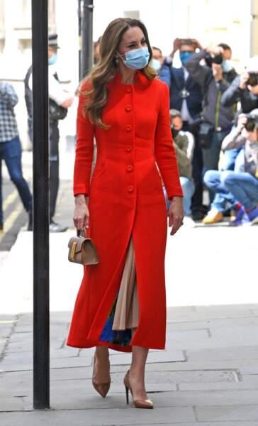 Kate Middleton, duchesse de Cambridge, dans son long manteau rouge et un sac à main en cuir DeMellier
