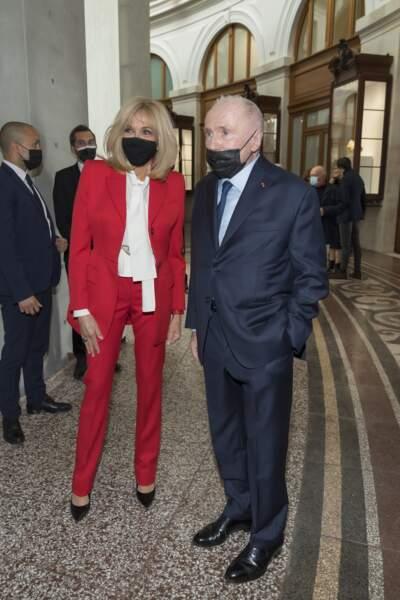 Brigitte Macron très élégante en costume d'homme et blouse à col lavallière Alexander McQueen le 19 mai 2021.