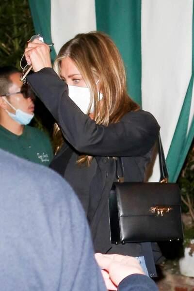 Jennifer Aniston mise aussi sur la sobriété d'un sac noir, rigide et porté épaule pour ce look qui balance entre style et décontraction.