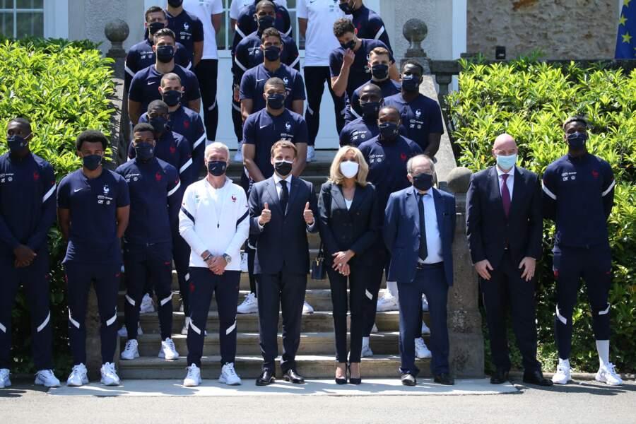 Brigitte Macron a le sens du style avec ce costume bleu marine et son t-shirt blanc col V.