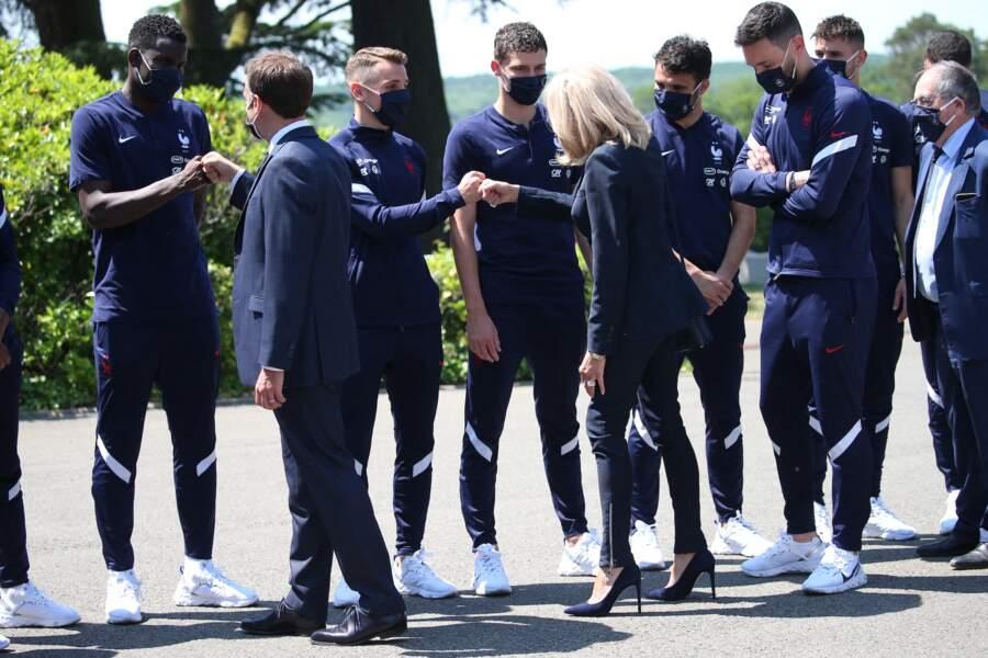 Brigitte Macron chic avec son pantalon slim zippé et ses escarpins bleu marine.