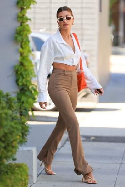 Hailey Bieber Baldwin reine du style s'approprie à merveille la tendance des tongs à talons associées à une chemise crop top et un pantalon beige