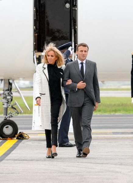 Brigitte Macron offre un look noir et blanc très sobre avec un manteau long en tweed signé Chanel.