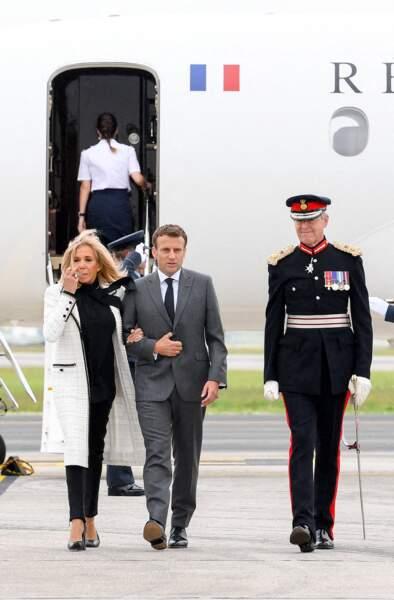 Brigitte Macron porte un long manteau en tweed blanc, un pull col lavallière, un slim noir, une paire d'escarpins