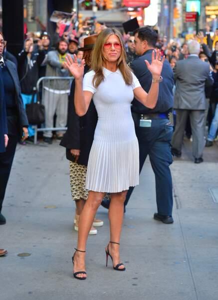 Jennifer Aniston en robe blanchedont la jupe est plissée.