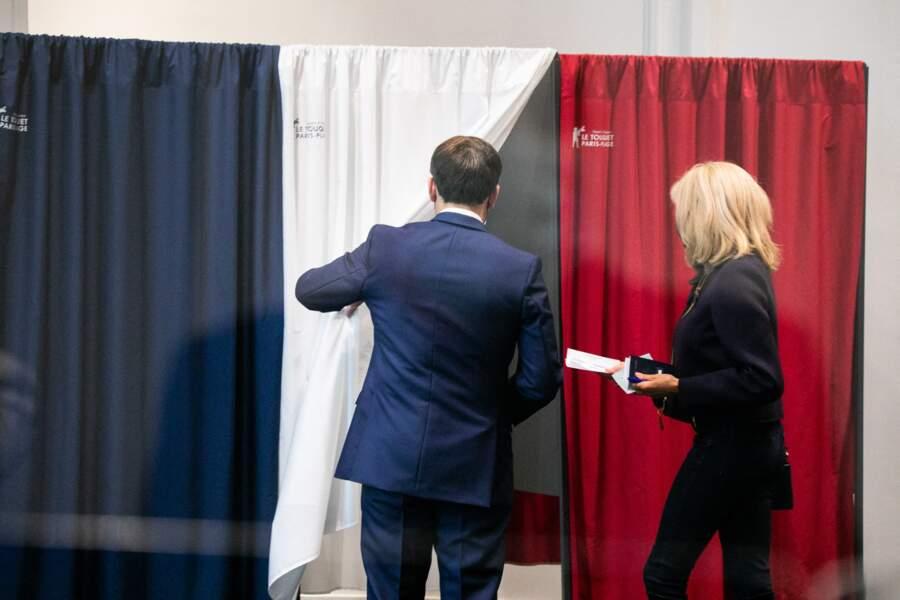 Le président de la république Emmanuel Macron ouvre le rideau à la Première dame, qui s'apprête à voter.