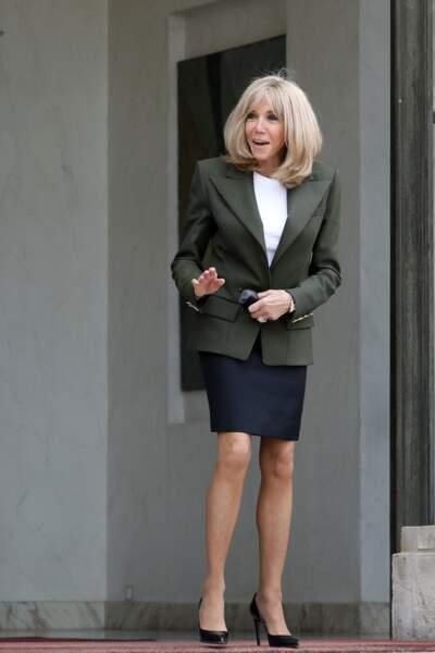 Brigitte Macron mixe de nombreuses couleurs pour ce look : du bleu marine, du kaki, du blanc et du noir.