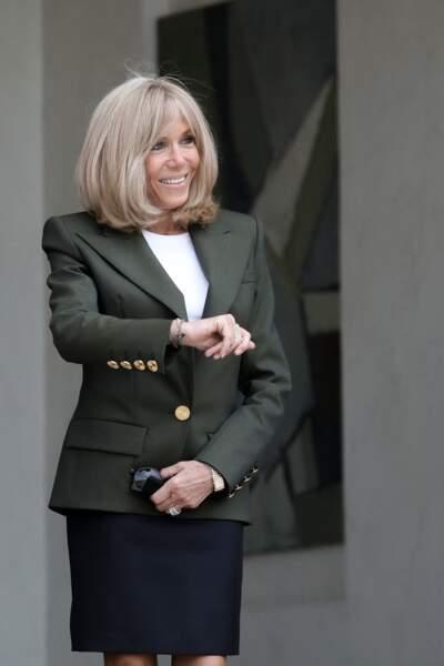 Brigitte Macron très chic en veste de costume kaki et jupe bleue marine.