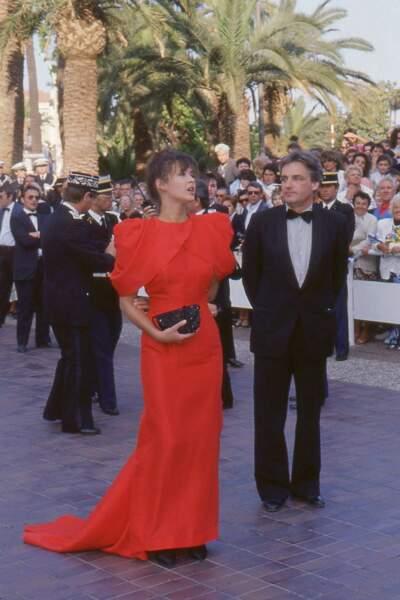 Sophie Marceau dans une robe rouge à maxi épaulettes, au côté de son compagnon et pygmalion Andrzej Zulawski, au Festival de Cannes en 1987.