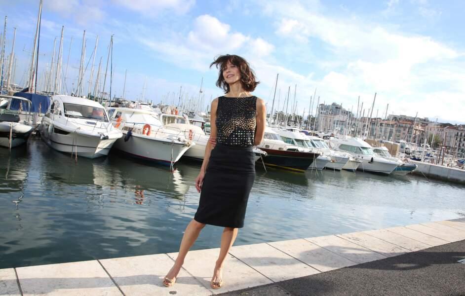Sophie Marceau en jupe noire midi et top lumineux sans manche à Cannes en 2014.