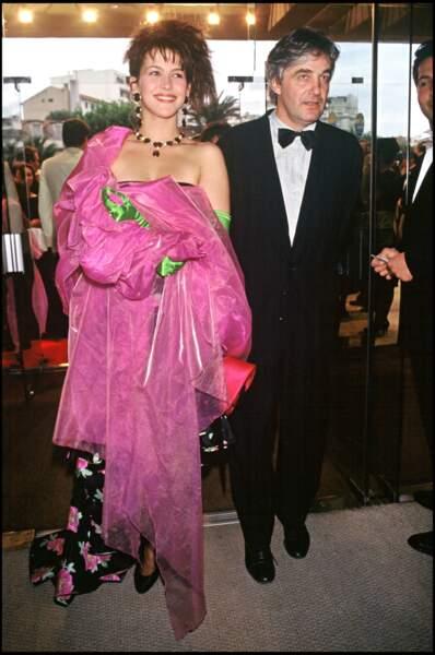 Sophie Marceau habillée d'une robe à fleurs, gantée de vert et drapée dans une étole shocking pink, au côté de son compagnon et pygmalion Andrzej Zulawski, au Festival de Cannes, en 1988.