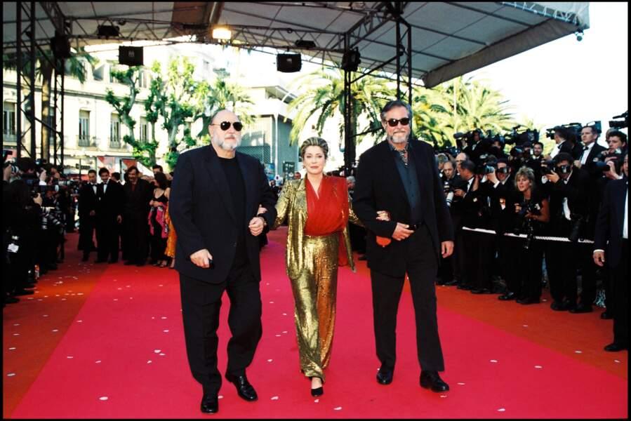 Catherine Deneuve en costume pailleté or et blouse en mousseline rouge Yves Saint Laurent, au Festival de Cannes, en 2000.