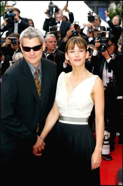 Sophie Marceau, avec son compagnon Jim Lemley, simplement élégante dans une robe noire et blanche... malgré un accident de bretelle qui suscitera l'émoi au Festival de Cannes, en 2005.