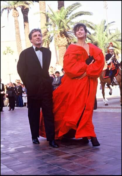 Sophie Marceau impériale dans un manteau en taffetas rouge, au côté de son compagnon et pygmalion Andrzej Zulawski, au Festival de Cannes, en 1987.