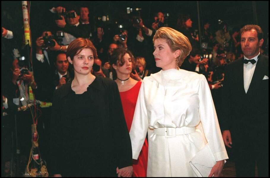 Catherine Deneuve en robe blanche Yves Saint Laurent, avec sa fille Chiara Mastroianni, au Festival de Cannes, en 1994.