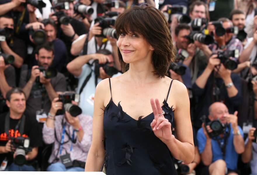Sophie Marceau mutine dans une robe bleu nuit à fines bretelles et plumes, au Festival de Cannes, en 2015.