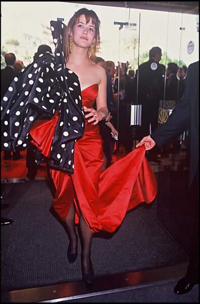 Sophie Marceau dans une robe bustier rouge et un boléro bouffant à pois signés Ungaro, au Festival de Cannes, en 1992.