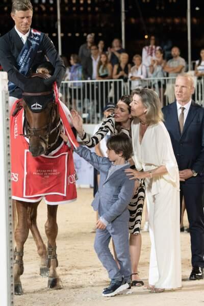 La princesse Caroline, Charlotte Casiraghi et Raphaël Elmaleh admirent un cheval.