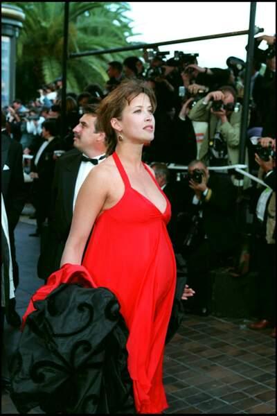 Sophie Marceau dans une robe empire rouge, parfaite pour mettre en valeur son ventre de futur maman, au Festival de Cannes, en 1995.
