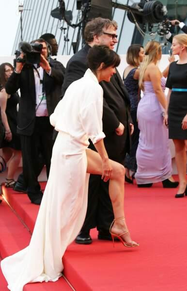 Sophie Marceau dévoilant son jeu de jambes dans sa robe portefeuille en soie blanche Alexandre Vauthier, au Festival de Cannes, en 2015.