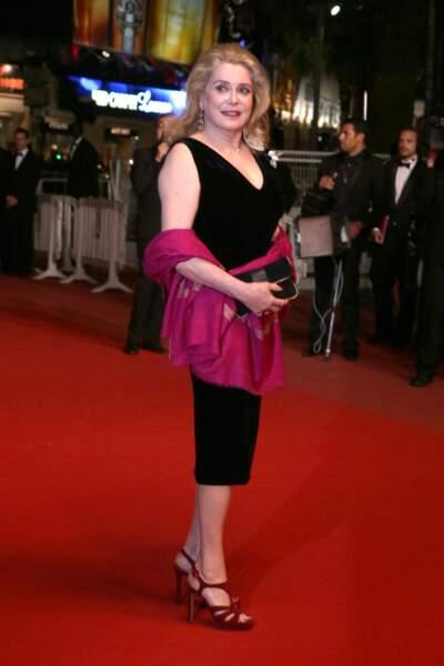 Catherine en robe noire décolletée et pachmina fuschia assortie à ses sandales, au Festival de Cannes, en 2013.