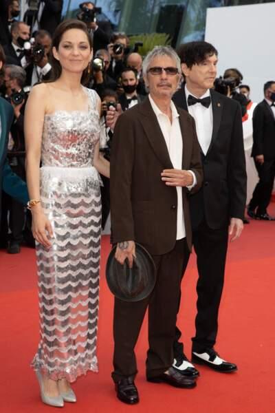 """Aux côtés de Leos Carax et Russel Mael, Marion Cotillard a pris la pose, très chic dans une robe Chanel argentée, pour la montée des marches du film """"Annette"""" lors de la cérémonie d'ouverture du 74ème Festival International du Film de Cannes, le 6 juillet 2021"""