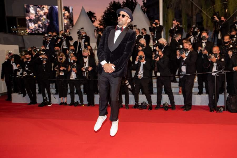 L'artiste JR a tenté un petit saut lors du photocall de la montée des marches du Festival de Cannes ce 10 juillet