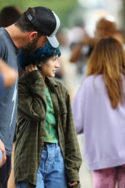 Les cheveux bleus bouclés et la chemise à carreaux extra-large, Emme Muniz maîtrise avec brio le style grunge, lors d'une séance shopping dans les Hamptons à New York, le mardi 6 juillet 2021