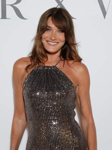 Carla Bruni en robe lamée Celine et maquillage Dior au dîner Dior à Cannes le 10 juillet 2021.