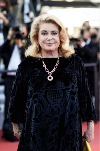 Catherine Deneuve en robe longue de velours noire à Cannes le 10 juillet 2021