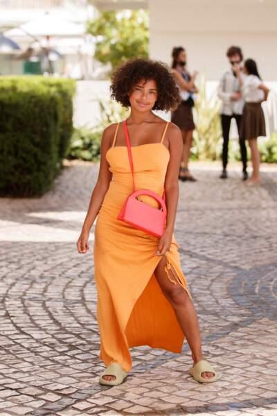 Paola Locatelli ose les sandales plates et porte un sac Medesisters ainsi qu'une robe orange fendue au 74ème Festival International du Film de Cannes