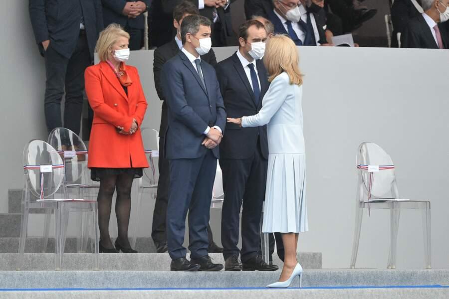 Avant de s'installer au côté du président de la République, Brigitte Macron a pris le temps de saluer les ministres présents, à l'instar de Gérald Darmanin, le 14 juillet 2021.
