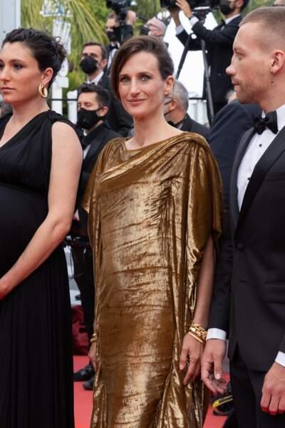 Camille Cottin, radieuse, en longue robe toge et manches kimono en velours bronze signée Dior.