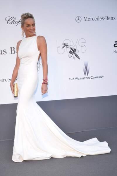 Sharon Stone à l'Amfar en 2013 : elle fait sensation en robe longue blanche moulante et dotée d'une traine.