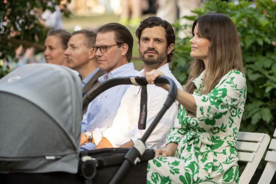"""Assise aux côtés de son époux, le prince Carl Philip, la princesse Sofia de Suède écoute attentivement le concert """"Solliden Sessions"""", au château de Solliden à Borgholm, le 13 juillet 2021"""