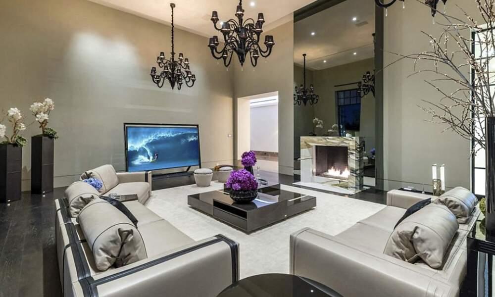 Décoré de grands chandeliers, d'une cheminée en marbre et d'un imposant miroir, ce coin salon est l'une des pièces fortes de cette villa décorée par la marque Fendi