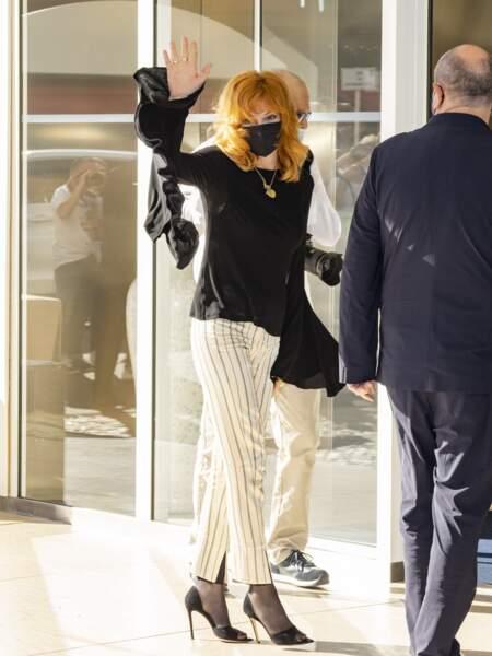 Mylène Farmer a associé son haut à manches évasées JW Anderson à un pantalon 7/8ème rayé signé Ann Demeulemeester et une paire  d'escarpins noirs Gianvito Rossi, à son arrivée au dîner du jury du 74ème Festival de Cannes, le 5 juillet 2021