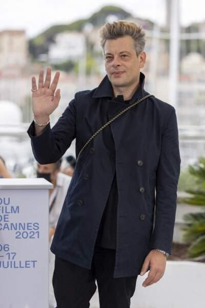 Benjamin Biolay, souriant, salue les photographes et le public venu le voir (de loin) au Festival de Cannes.