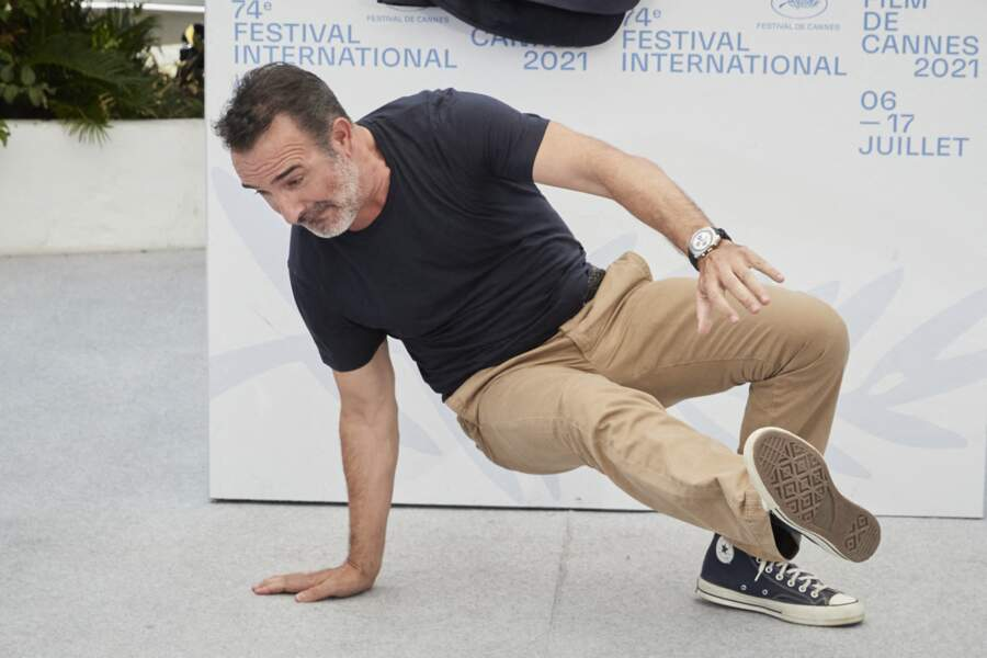 Jean Dujardin en train de faire une acrobatie au photocall du film Oss 117, le 17 juillet