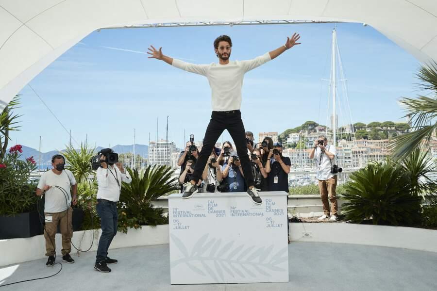 Pierre Niney en train de sauter du décor pendant le photocall du film Oss 117, le 17 juillet